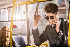 Handsome smiling young businessman in sunglasses talking on smartphone. In city bus Stock Image