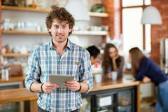 Handsome smiling young curly man holding laptop stansing in hostel Stock Image