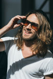 Handsome smiling young man adjusting sunglasses and looking away Stock Photo