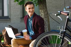Handsome smiling young man with coffee to go using laptop and looking away. On bench royalty free stock photography