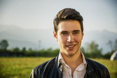 Handsome smiling young man at countryside, in Royalty Free Stock Photos