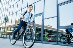 Handsome smiling young man in eyeglasses and formal wear riding bike. On street stock photography