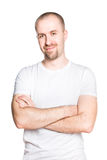 Handsome smiling young man with folded arms in white t-shirt. Vertical portrait of a handsome smiling young man with folded arms in a white t-shirt isolated on Royalty Free Stock Photography