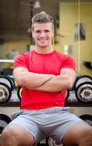 Handsome smiling young man in gym sitting on dumbbells rack Stock Photos