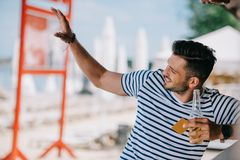 Handsome smiling young man holding beer bottle and credit card while waving hand. And looking away stock photography