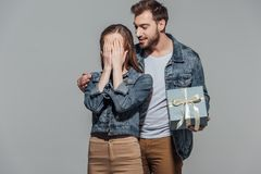 Handsome smiling young man holding gift box while his girlfriend closing eyes. Handsome smiling young men holding gift box while his girlfriend closing eyes Royalty Free Stock Photo