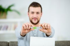 Handsome smiling young man at home showing usb key royalty free stock images