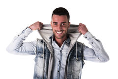 Handsome smiling young man with hoodie and denim vest Royalty Free Stock Image