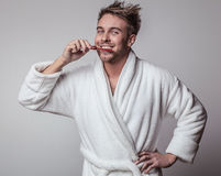 Handsome smiling young man in luxurious bathrobe. Stock Images