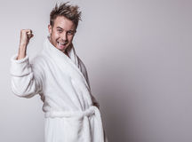 Handsome smiling young man in luxurious bathrobe. Royalty Free Stock Photos