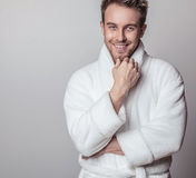 Handsome smiling young man in luxurious bathrobe. Stock Image
