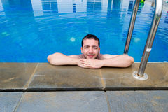 Handsome smiling young man relaxing in the swimming pool Royalty Free Stock Photos