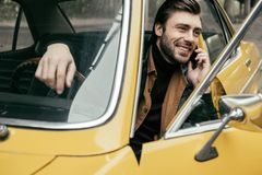 Handsome smiling young man talking by smartphone while sitting in yellow. Vintage car royalty free stock photography