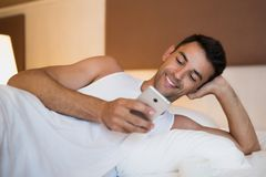 Handsome smiling young man using a mobile phone and messaging in. The white bed. On bedroom background Stock Images