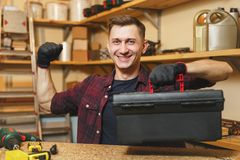 Handsome smiling young man working in carpentry workshop at wooden table place with piece of wood. Handsome strong charismatic caucasian young man in plaid shirt Royalty Free Stock Photo