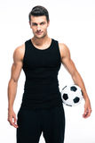 Handsome soccer player holding ball Stock Photography