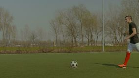 Handsome soccer player taking a penalty kick stock footage