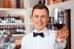 Handsome sommelier holding glass of wine Stock Image