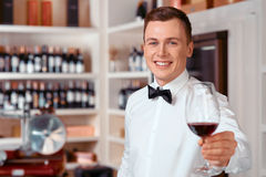 Handsome sommelier holding glass of wine. Full of positivity. Handsome vivacious smiling sommelier holding wine glass and going to taste it while being involved stock photo