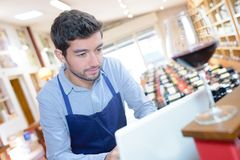 Handsome sommelier ordering wine on computer at store. Handsome stock images