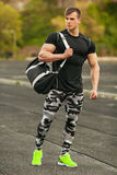 Handsome sport man in sportswear outdoor. Athletic male outside Stock Photos