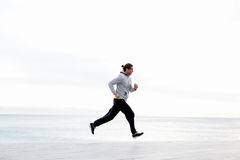 Handsome sportive man running in the beach in early morning Stock Photography
