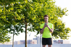 Handsome sports man preparing for his diary morning jog outdoors. Half length portrait of caucasian male runner choosing the music on his smartphone playlist for Royalty Free Stock Image