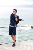 Handsome sports man stretching hands outdoors Stock Photos