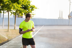 Handsome sports man using his mobile phone while listening to music and having a rest during morning jog in urban park Royalty Free Stock Image