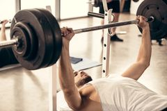 handsome sportsman lifting barbell with heavy weight plates royalty free stock photo