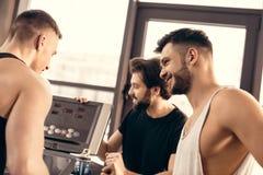 handsome sportsmen setting treadmill royalty free stock photos