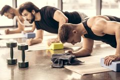 handsome sportsmen simultaneously doing plank and using blocks stock photo