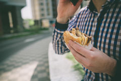 Handsome sporty bearded dark-haired man eating a hamburger and talking on the phone Stock Photos
