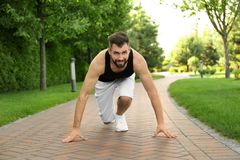 Handsome sporty man in starting position for running. Outdoors Stock Image