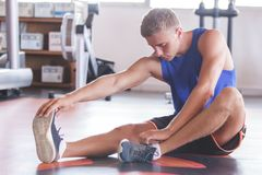 Handsome sporty man stretching his feet Stock Images