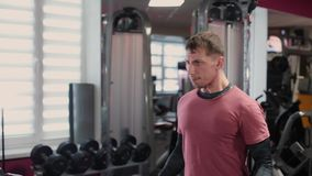 Handsome sporty man training dumbbell biceps in the gym. stock footage