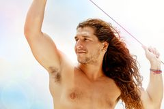 A handsome sporty guy with long hair against a blue clear sky with white clouds. Light background. Journey on a yacht by sea. Travel image. Vacation concept stock images