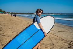 Handsome sporty young surfer posing with his surfboard under his. Arm in his wetsuit on a sandy tropical beach Royalty Free Stock Images