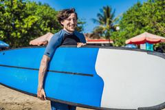 Handsome sporty young surfer posing with his surfboard under his. Arm in his wetsuit on a sandy tropical beach Royalty Free Stock Photos