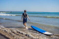 Handsome sporty young surfer posing with his surfboard under his. Arm in his wetsuit on a sandy tropical beach Royalty Free Stock Photography