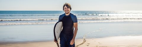 Handsome sporty young surfer posing with his surfboard under his arm in his wetsuit on a sandy tropical beach BANNER long format. Handsome sporty young surfer Royalty Free Stock Photography