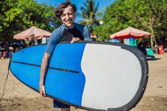 Handsome sporty young surfer posing with his surfboard under his. Arm in his wetsuit on a sandy tropical beach Royalty Free Stock Image