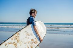 Handsome sporty young surfer posing with his surfboard under his. Arm in his wetsuit on a sandy tropical beach Stock Image