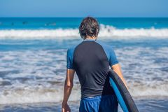 Handsome sporty young surfer posing with his surfboard under his. Arm in his wetsuit on a sandy tropical beach Stock Images