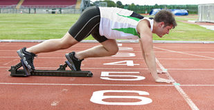 Handsome sprinter on the starting line in stadium. Handsome sprinter on the starting line putting his foot in the starting block in a stadium Royalty Free Stock Images