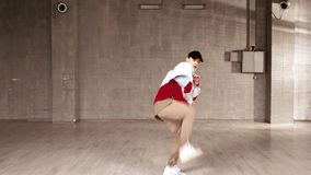 Handsome street dancer performing contemporary dance. Stylish energetic man in denim jacket and cap dancing hip-hop indoor stock footage