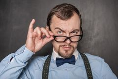 Handsome strict teacher in eyeglasses looking at you. On blackboard background stock photo