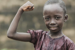 Handsome Strong African Boy showing muscles on blurred isolated background. Little african boy showing muscles and looking at camera with blurred background Stock Photos