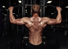 Handsome strong athletic man pumping up back muscles. Muscular bodybuilder with naked sport torso doing exercises in gym. stock photos