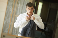Handsome and strong man putting on official suit. Nice and slender groom wearing wedding suit and putting on cuffs in bedroom looking in mirror Stock Photos